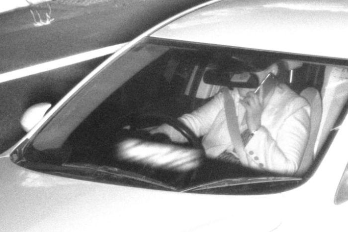 persona che usa lo smartphone alla guida